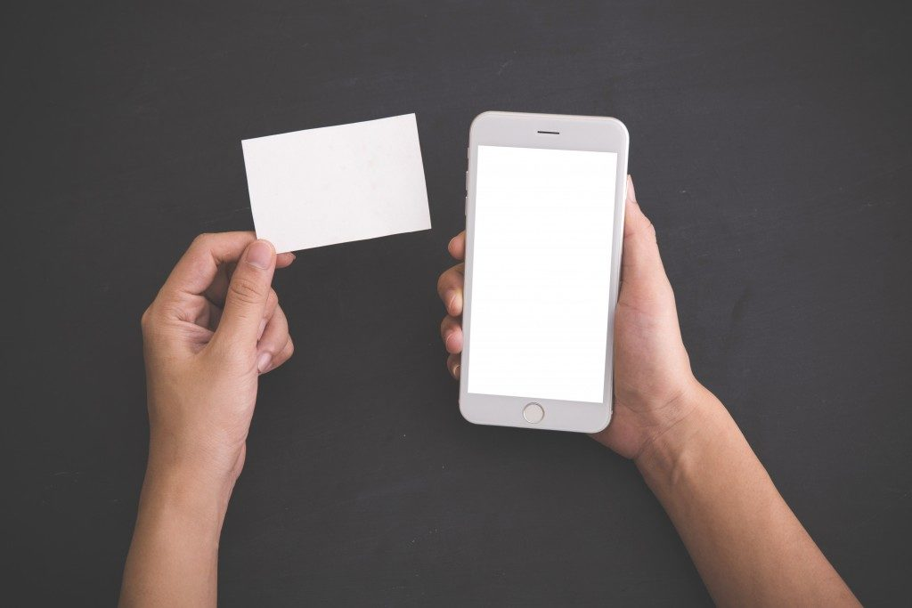 person holding a blank card and a phone