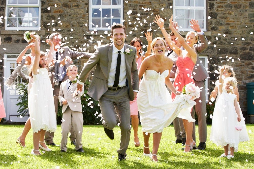 Guests throwing confetti over bride and groom