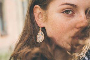woman wearing an earing with green diamonds